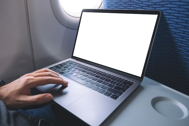 기내에 앉아있는 동안 빈 흰색 바탕 화면 화면이있는 노트북 컴퓨터 터치 패드를 사용하고 만지는 남자의 모형 이미지