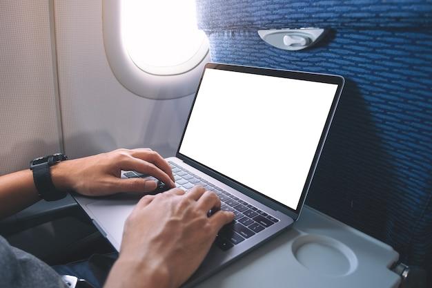오두막에 앉아있는 동안 빈 흰색 바탕 화면이있는 랩톱 컴퓨터를 사용하고 입력하는 남자의 모형 이미지