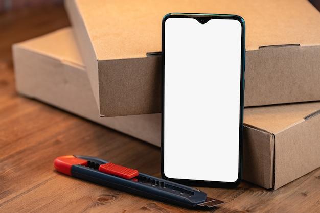 Изображение макета смартфона с пустым белым экраном среди посылок и резаком на деревянном столе.