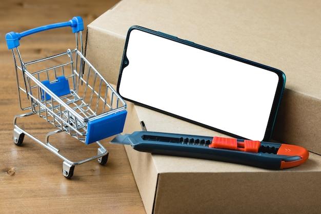 Изображение макета смартфона с пустым белым экраном среди посылок, тележки для покупок и резака для коробок на деревянном столе.
