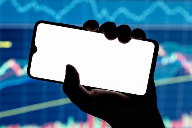 握りしめた手に空白の白い画面と背景に株価チャートを持つスマートフォンのモックアップ画像。
