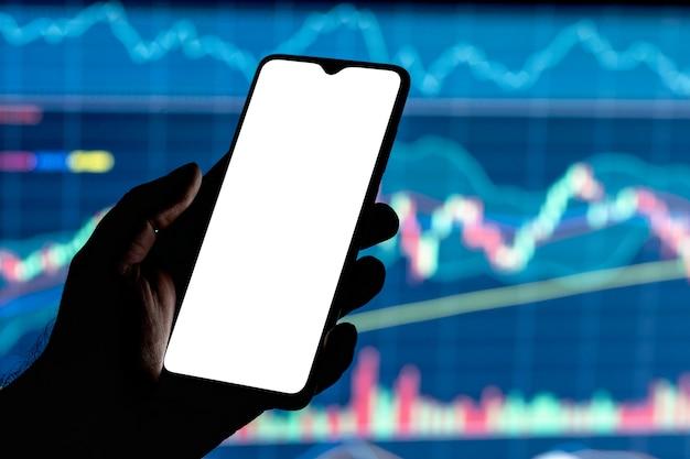 手に空白の白い画面と背景に株価チャートを持つスマートフォンのモックアップ画像。