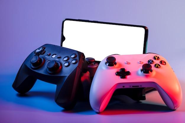 게임패드 더미에 빈 흰색 화면이 있는 스마트폰의 모형 이미지.