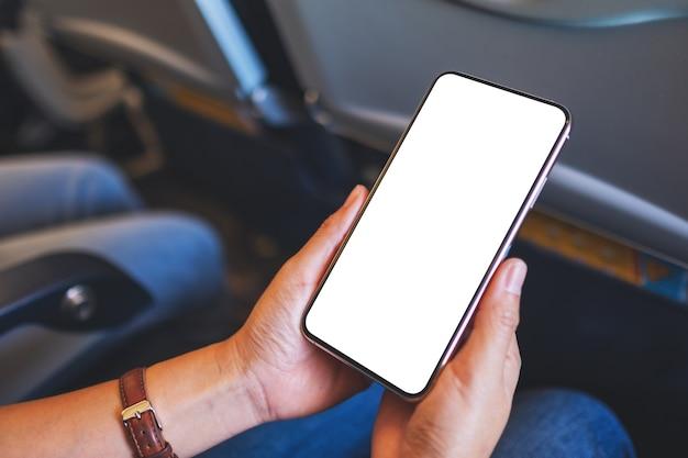 Макет изображения женщины, держащей черный мобильный телефон с пустым экраном рабочего стола в самолете