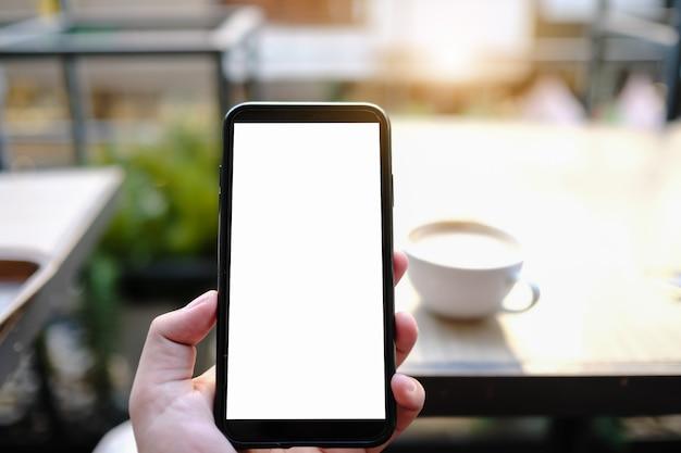 保持し、カフェで空白の画面を持つ黒い携帯電話を示す女性のモックアップ画像。
