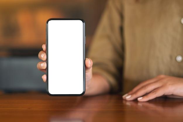 カフェのテーブルに空白の白い画面で黒い携帯電話を持って見せている女性のモックアップ画像