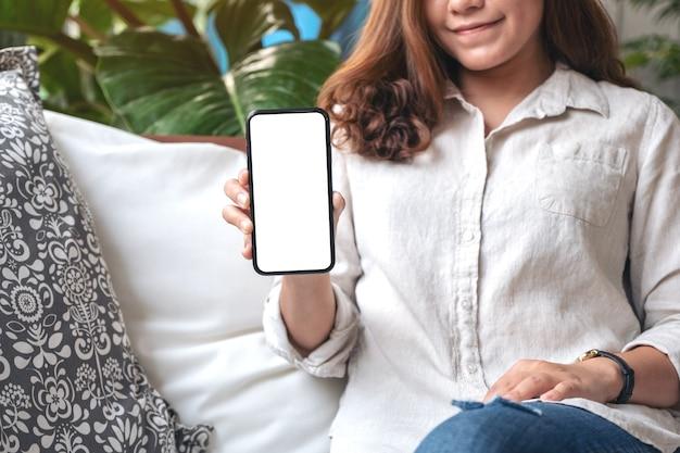 モダンなカフェのテーブルに空白の白い画面で黒い携帯電話を持って見せている女性のモックアップ画像