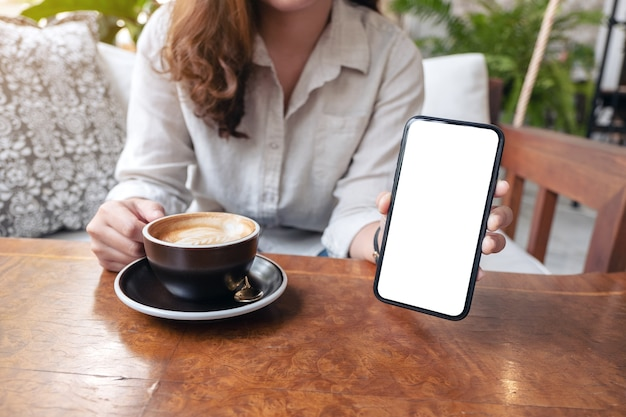 カフェでコーヒーを飲みながら、空白の白い画面で黒い携帯電話を持って見せている女性のモックアップ画像