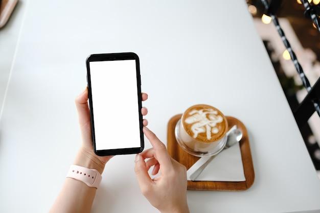 保持し、黒い携帯電話を示す女性のモックアップ画像