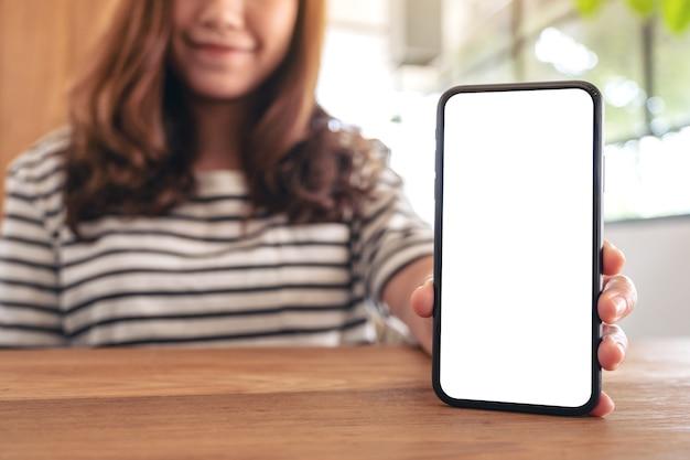 木製のテーブルに空白の画面で白い携帯電話を持って見せている女性のモックアップ画像