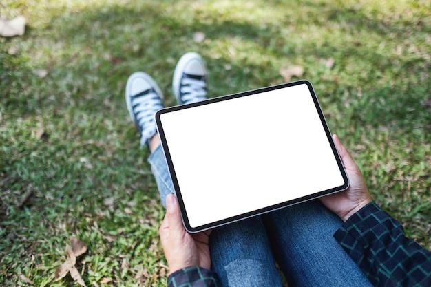 Макет изображения женщины, держащей и использующей черный планшетный пк с пустым белым экраном рабочего стола, сидя на открытом воздухе