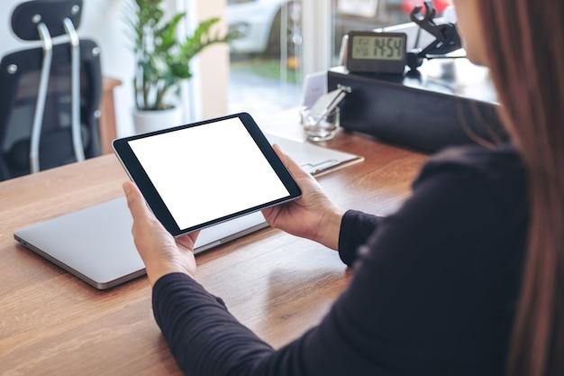 Макет изображения женщины, держащей и использующей черный планшетный пк с пустым белым экраном рабочего стола