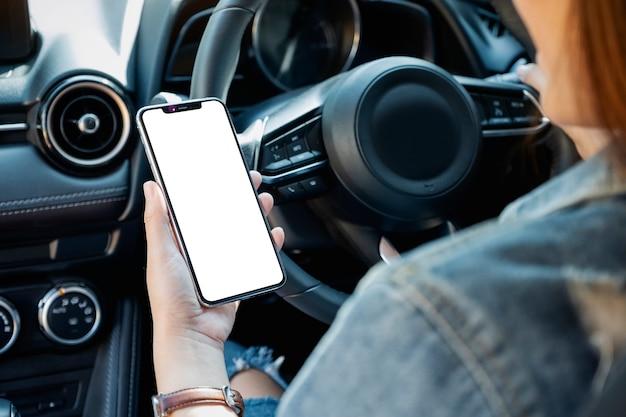 車の運転中に空白の画面で携帯電話を保持して使用している女性のモックアップ画像