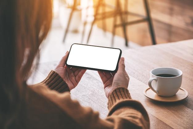 탁자 위에 커피 컵이 있는 수평으로 빈 데스크탑 화면이 있는 검은색 휴대폰을 들고 있는 여성의 흉내낸 이미지