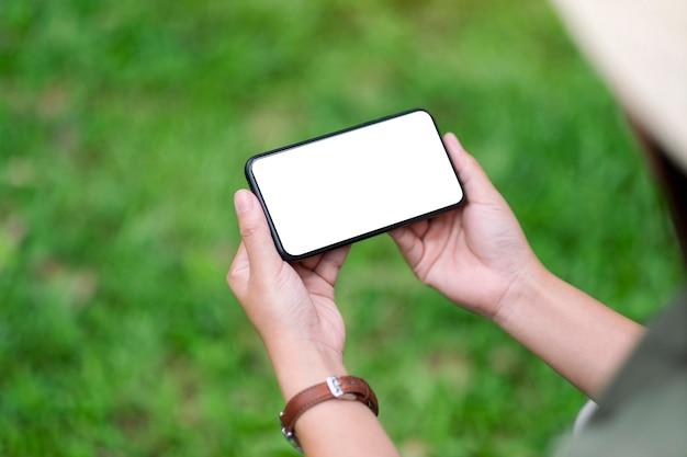 공원에서 빈 데스크탑 화면이 있는 검은색 휴대폰을 들고 있는 여성의 모형 이미지