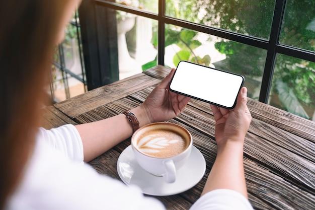 탁자 위에 커피 컵이 있는 빈 데스크탑 화면이 있는 검은색 휴대폰을 들고 있는 여성의 흉내낸 이미지