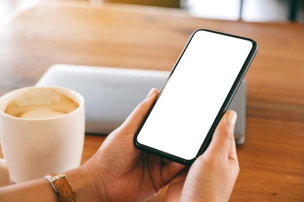 탁자 위에 노트북과 커피 컵이 있는 빈 데스크탑 화면이 있는 검은색 휴대폰을 들고 있는 여성의 흉내낸 이미지