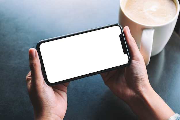 탁자 위에 커피 컵이 있는 빈 화면이 있는 검은색 휴대폰을 들고 있는 여성의 흉내낸 이미지