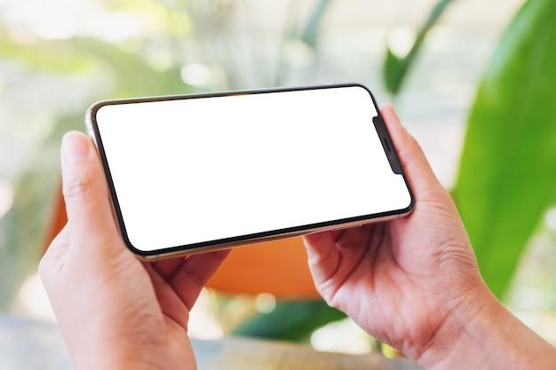 木製のテーブルにコーヒーカップと空白の画面で黒い携帯電話を保持している女性のモックアップ画像