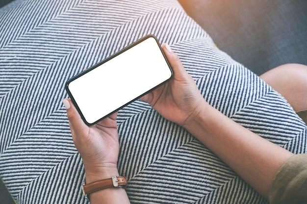 リラックスした気分でリビングルームに座っている間、空白の白いデスクトップ画面で黒い携帯電話を水平に保持している女性のモックアップ画像