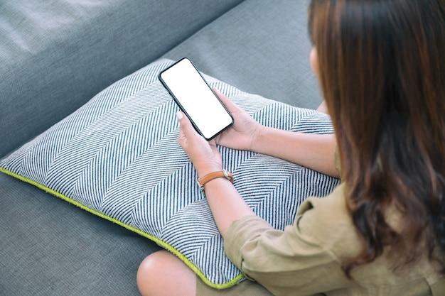 リラックスした気分でリビングルームに座っている間空白の白いデスクトップ画面で黒い携帯電話を保持している女性のモックアップ画像