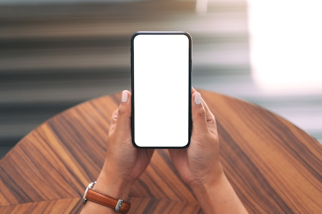 나무 테이블 배경으로 빈 흰색 바탕 화면 화면으로 검은 휴대 전화를 들고 여자의 모형 이미지