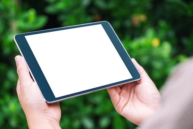 Макет изображения женщины, держащей черный планшетный пк с пустым белым экраном рабочего стола в парке