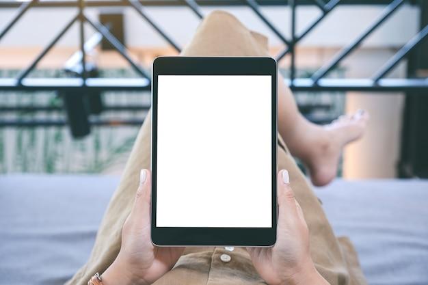 Макет изображения женщины, держащей черный планшетный пк с пустым белым экраном рабочего стола, лежа в гостиной с чувством расслабленности