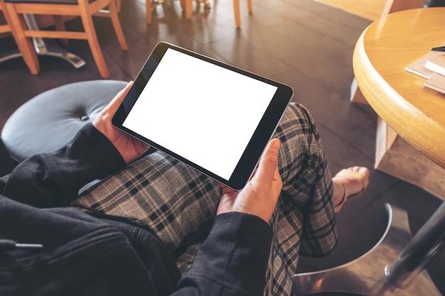 Макет изображения женщины, держащей черный планшетный пк с пустым белым экраном по горизонтали, сидя в кафе