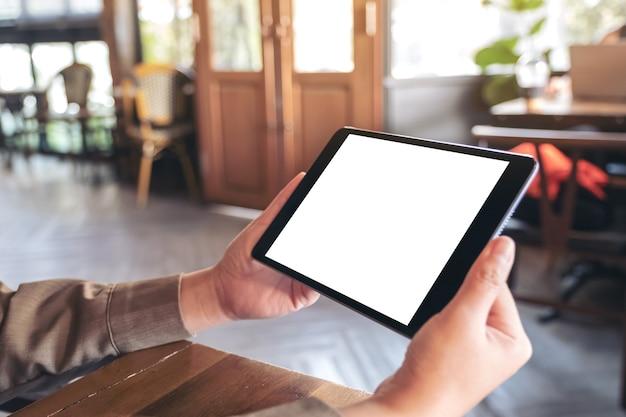 카페에 앉아있는 동안 가로로 빈 흰색 화면이 검은 태블릿 pc를 들고 여자의 모형 이미지