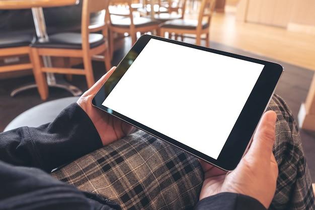 Макет изображения женщины, держащей черный планшетный пк с пустым белым экраном, сидя в кафе