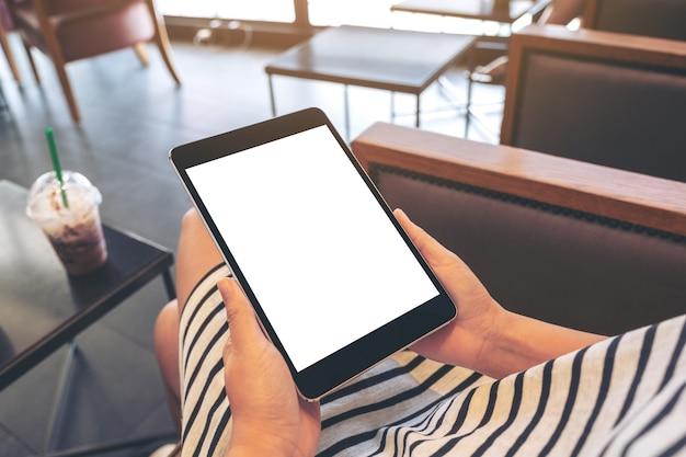 카페에 앉아있는 동안 빈 흰색 화면이 검은 태블릿 pc를 들고 여자의 모형 이미지