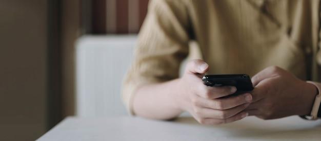 カフェで空白の黒い画面で携帯電話を持っている女性のモックアップ画像