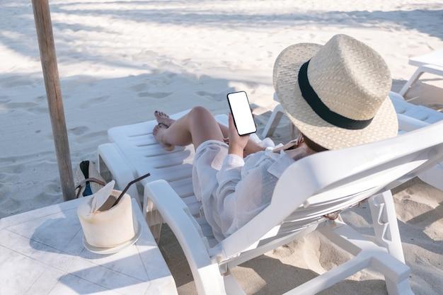 ビーチのビーチチェアに横になっている間空白のデスクトップ画面で白い携帯電話を保持している女性のモックアップ画像