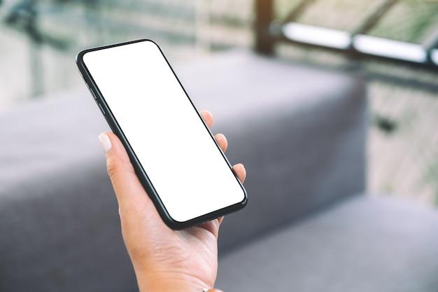 Макет изображения руки женщины, держащей черный мобильный телефон с пустым белым экраном рабочего стола, сидя в гостиной и чувствуя себя расслабленным