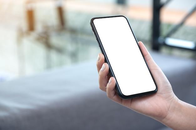 Макет изображения женской руки, держащей черный мобильный телефон с пустым белым экраном рабочего стола