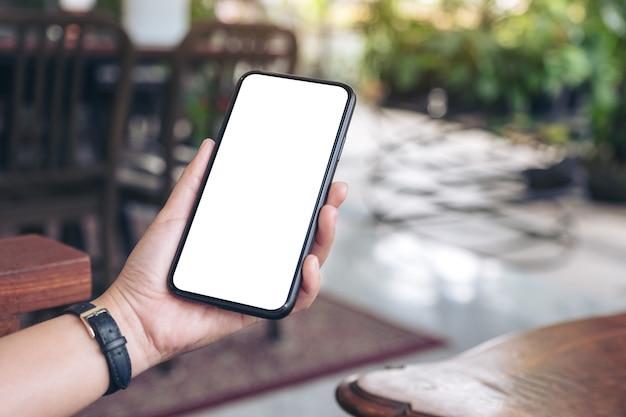 Макет изображения женской руки, держащей черный мобильный телефон с пустым белым экраном