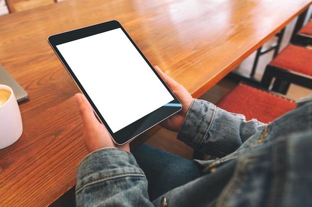 Макет изображения женщины, сидящей и держащей черный планшетный пк с пустым белым экраном рабочего стола по горизонтали