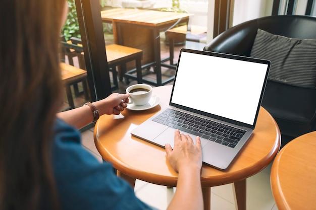 コーヒーを飲みながら空白の白いデスクトップ画面でノートパソコンのタッチパッドを使用して触れている女性のモックアップ画像