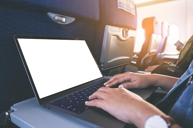 기내에 앉아있는 동안 빈 흰색 바탕 화면이있는 랩톱 컴퓨터를 사용하고 입력하는 여자의 모형 이미지