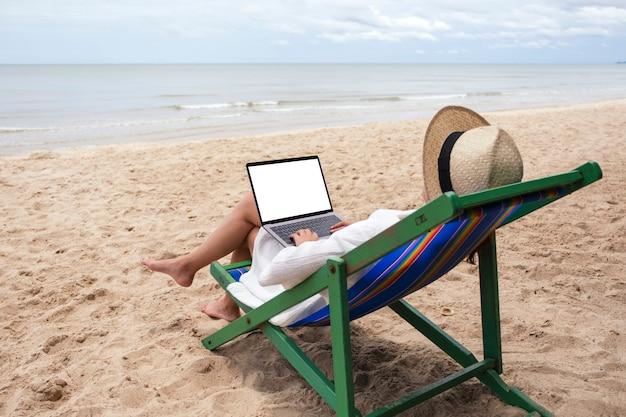 ビーチチェアに横になっている間、空白のデスクトップ画面でラップトップコンピュータを使用して入力している女性のモックアップ画像
