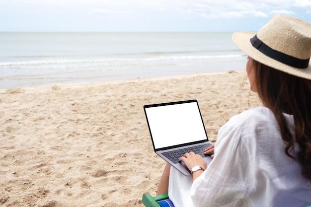 ビーチチェアに座っている間、空白のデスクトップ画面でラップトップコンピュータを使用して入力している女性のモックアップ画像