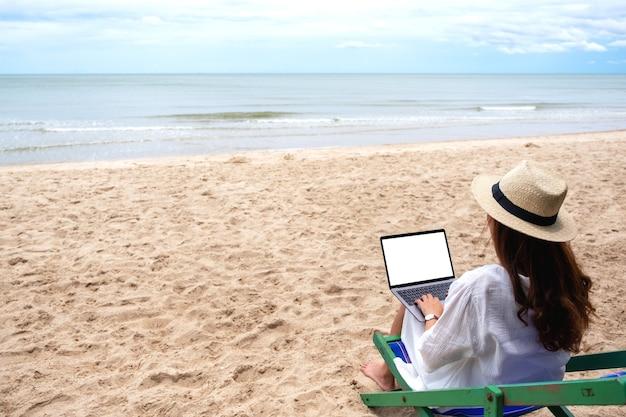 ビーチのビーチチェアに座っている間、空白のデスクトップ画面でラップトップコンピューターを使用して入力している女性のモックアップ画像