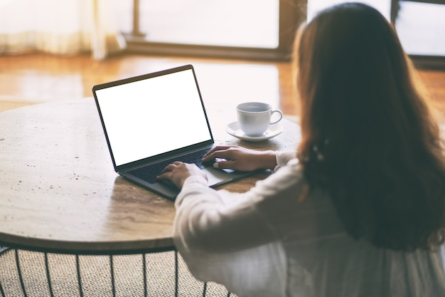 Макет изображения женщины, использующей и печатающей на ноутбуке с пустым белым экраном рабочего стола на столе, сидя на полу в доме