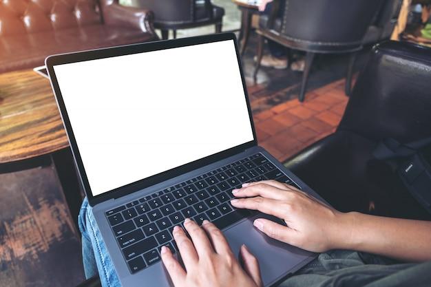 カフェに座っているときに空白の白いデスクトップ画面を備えたラップトップを使用して入力する女性のモックアップ画像