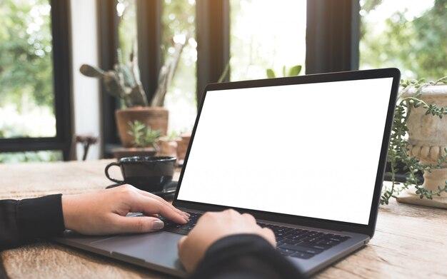 Макет изображения женщины с помощью и набрав на ноутбуке с пустой белый экран рабочего стола с чашкой кофе на деревянный стол в кафе
