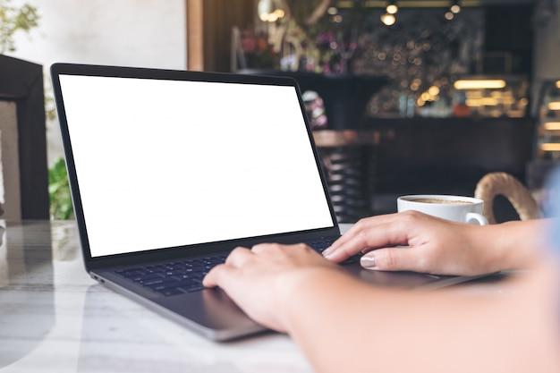Макет изображения женщины с помощью и набрав на ноутбуке с пустой белый экран и чашка кофе на столе в современном кафе