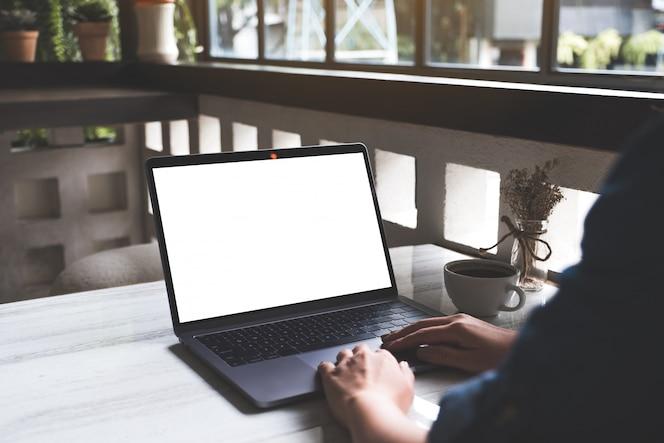 현대 카페에서 테이블에 빈 흰색 화면과 커피 컵 노트북에 입력하고 사용하는 여자의 모형 이미지