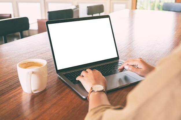 空白の白い画面と木製のテーブルの上のコーヒーカップとラップトップを使用して入力している女性のモックアップ画像