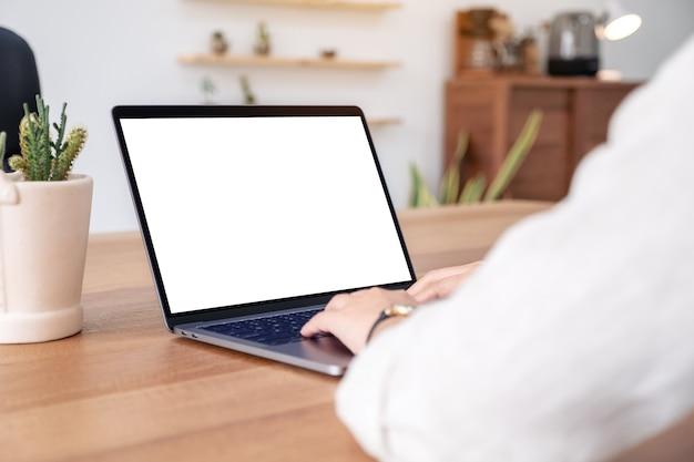 나무 테이블에 빈 흰색 화면이 노트북을 사용하고 입력하는 여자의 모형 이미지